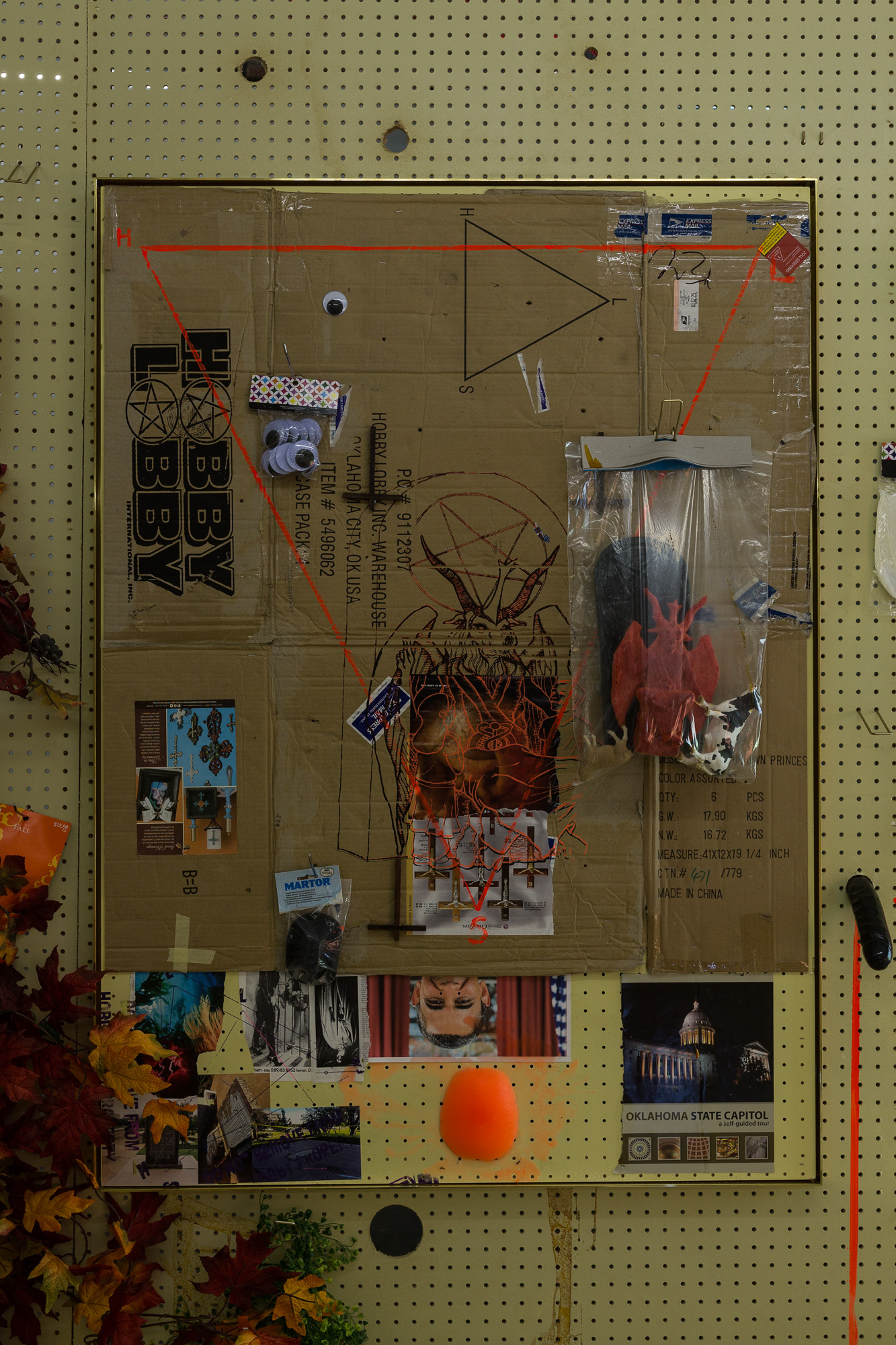 Stephen G. Rhodes Lobber IV, 2014 paint,collage elements on HL pegboard, baphomet satanic proposal toy kit, Hobby Lobby merchandise, wax scalp, Hobby Lobby box, OKC courthouse brochure, 10 commandments photos 141 x 102 cm 55 1/2 x 40 1/8 ins. The Eleventh Hobby , Stephen G. Rhodes